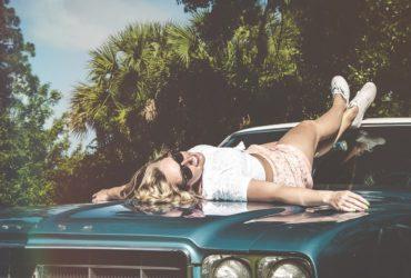 girl lying on a car